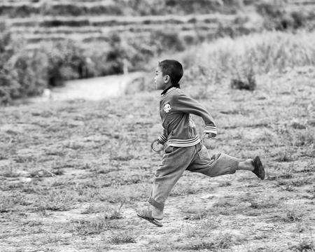 sapa: SAPA, VIETMAN - SEP 22, 2014: Unidentified Hmong boy runs on the grass in Sapa, Vietnam. Hmong is a minority ethnic group of Vietnam Editorial