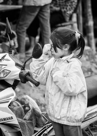minority: TA PHIN, VIETMAN - SEP 12, 2014: Unidentified girl near a motorbike in the village of Vietnam. Red Dao is a minority ethnic group of Vietnam