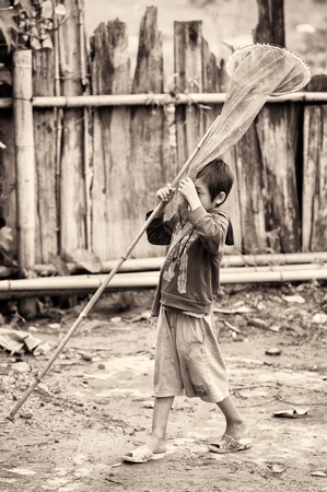 fish net: TA PHIN, VIETMAN - SEP 12, 2014: Unidentified boy runs with a fish net in the village of Vietnam. Red Dao is a minority ethnic group of Vietnam
