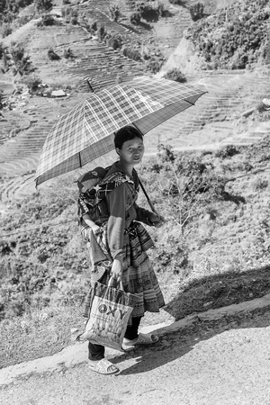 sapa: SAPA, VIETMAN - SEP 22, 2014: Unidentified Hmong woman carries her baby in Sapa, Vietnam. Hmong is a minority ethnic group of Vietnam