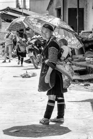 vietnamese ethnicity: LAO CHAI, VIETMAN - SEP 12, 2014: Unidentified Black Hmong woman with her baby on her back in the street in Lao Chai,  Vietnam. Hmong is a ethnic minority in Vietnam Editorial