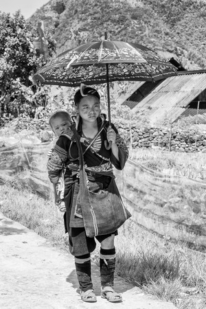 sapa: SAPA, VIETMAN - SEP 22, 2014: Unidentified Hmong woman carries her baby on her back in Sapa, Vietnam. Hmong is a minority ethnic group of Vietnam
