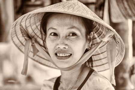 vietnamese ethnicity: HO CHI MIN, VIETMAN - OCT 4, 2014: Unidentified Vietnamese woman in a rice hat portrait in Saigon, Vietnam. 86 of Vietnamese people belong to the Viet ethnic group