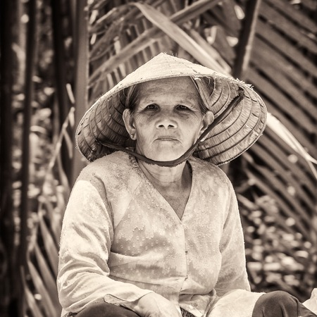 HO CHI MIN, VIETMAN - OCT 4, 2014: Unidentified Vietnamese woman in a rice hat portrait in Saigon, Vietnam. 86 of Vietnamese people belong to the Viet ethnic group