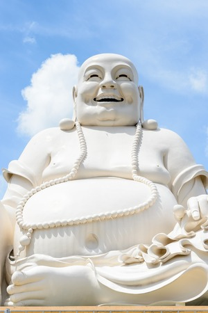 smiling buddha: MY THO, VIETNAM - OCT 5, 2014: Massive statue of the Sitting Smiling Buddha at the Vinh Tranh Pagoda in My Tho, the Mekong Delta,