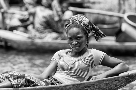 PORTO-NOVO, BENIN - MAR 9, 2012: Unidentified Beninese  woman lays in a wooden boat. People of Benin suffer of poverty due to the difficult economic situation.