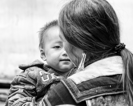 sa: SAPA, VIETMAN - SEP 22, 2014: Unidentified Hmong little boy on his mother arms in Sapa, Vietnam. Hmong is a minority ethnic group of Vietnam