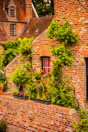 Medieval houses with flowers at the windows in the Historic Centre of Bruges, Belgium. Stock Photo