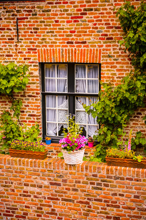 Medieval houses with flowers at the windows in the Historic Centre of Bruges, Belgium. part of the UNESCO World Heritage site