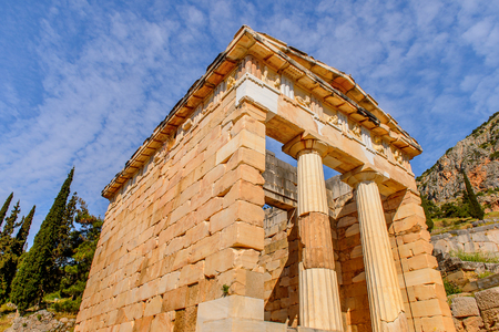 Athenian Treasury in Delphi, an archaeological site in Greece, at the Mount Parnassus. Delphi is famous by the oracle at the sanctuary dedicated to Apollo.