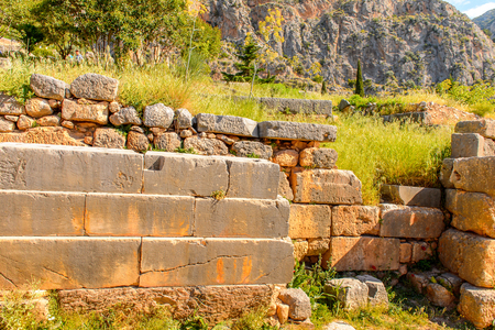 Ancient ruins of Delphi, an archaeological site in Greece, at the Mount Parnassus. Delphi is famous by the oracle at the sanctuary dedicated to Apollo. Stock Photo
