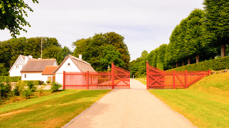 Small houses and the red fence in the park behind the Castle in Denmark