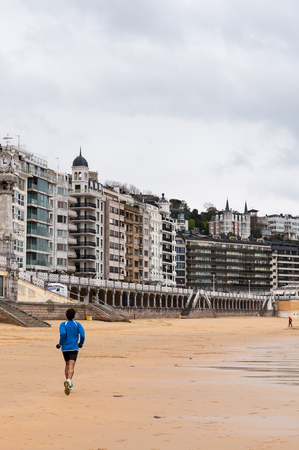 A young man runs over the Bay de la Concha, San Sebastian, Basque Country, Spain