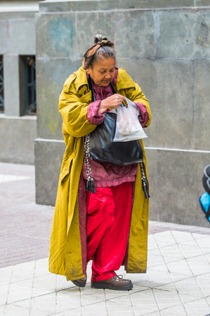 SANTIAGO, CHILE - NOV 1, 2014:  Unidentified Chilean poor woman in the street in Santiago. Chilean people are mainly of mixed Spanish and Amerindian descent