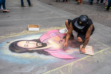 SANTIAGO, CHILE - NOV 1, 2014:  Unidentified Chilean man draws a Jesus Christ image on the ground in Santiago. Chilean people are mainly of mixed Spanish and Amerindian descent