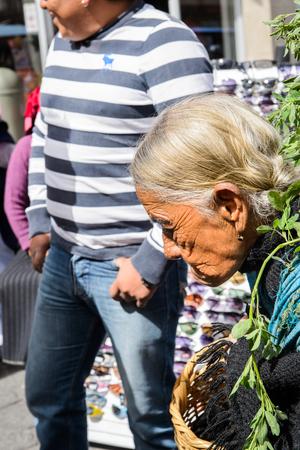 OTAVALO, ECUADOR - JAN 3, 2015: Unidentified Ecuadorian old woman carries a basket at the Otavalo Market. 71,9% of Ecuadorian people belong to the Mestizo ethnic group
