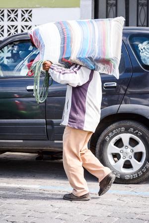 OTAVALO, ECUADOR - JAN 3, 2015: Unidentified Ecuadorian man walks with a bag at the Otavalo Market. 71,9% of Ecuadorian people belong to the Mestizo ethnic group