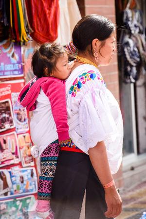 OTAVALO, ECUADOR - JAN 3, 2015: Unidentified Ecuadorian woman carries her little daughter at the Otavalo Market. 71,9% of Ecuadorian people belong to the Mestizo ethnic group
