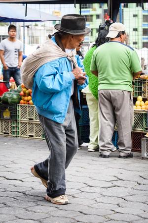 OTAVALO, ECUADOR - JAN 3, 2015: Unidentified Ecuadorian man works at the Otavalo Market. 71,9% of Ecuadorian people belong to the Mestizo ethnic group