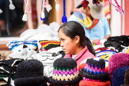 OTAVALO, ECUADOR - JAN 3, 2015: Unidentified Ecuadorian girl sells sewed hats at the Otavalo Market. 71,9% of Ecuadorian people belong to the Mestizo ethnic group