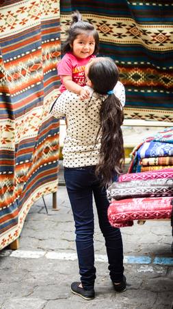 OTAVALO, ECUADOR - JAN 3, 2015: Unidentified Ecuadorian woman and her daughter at the Otavalo Market. 71,9% of Ecuadorian people belong to the Mestizo ethnic group