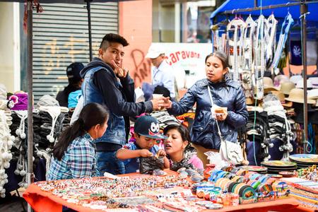 OTAVALO, ECUADOR - JAN 3, 2015: Unidentified Ecuadorian people work at the Otavalo Market. 71,9% of Ecuadorian people belong to the Mestizo ethnic group Editorial
