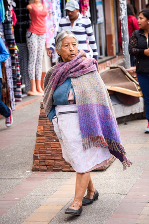 OTAVALO, ECUADOR - JAN 3, 2015: Unidentified Ecuadorian woman in traditional clothes works at the Otavalo Market. 71,9% of Ecuadorian people belong to the Mestizo ethnic group Editorial