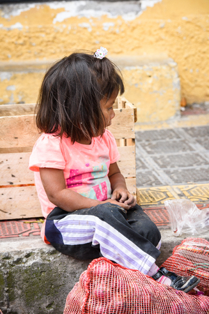 OTAVALO, ECUADOR - JAN 3, 2015: Unidentified Ecuadorian little girl with onions at the Otavalo Market. 71,9% of Ecuadorian people belong to the Mestizo ethnic group Editorial