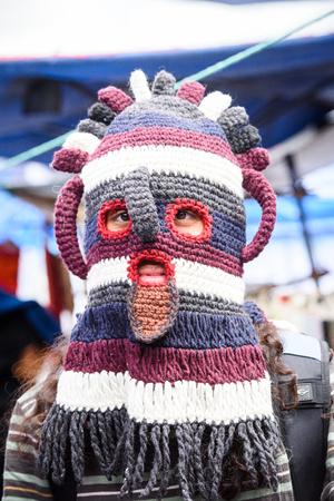 OTAVALO, ECUADOR - JAN 3, 2015: Unidentified Ecuadorian man in a funny hat at the Otavalo Market. 71,9% of Ecuadorian people belong to the Mestizo ethnic group