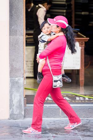 QUITO, ECUADOR - JAN 2, 2015: Unidentified Ecuadorian woman carries her child. 71,9% of Ecuadorian people belong to the Mestizo ethnic group