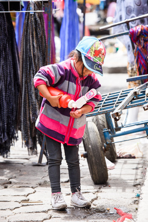 OTAVALO, ECUADOR - JAN 3, 2015: Unidentified Ecuadorian little girl at the Otavalo Market. 71,9% of Ecuadorian people belong to the Mestizo ethnic group
