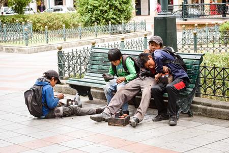 CUENCA, ECUADOR - JAN 9, 2015: Unidentified Ecuadorian children on a bench. 71,9% of Ecuadorian people belong to the Mestizo ethnic group Zdjęcie Seryjne - 93419127
