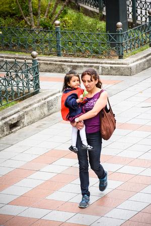 CUENCA, ECUADOR - JAN 9, 2015: Unidentified Ecuadorian woman carries her baby. 71,9% of Ecuadorian people belong to the Mestizo ethnic group