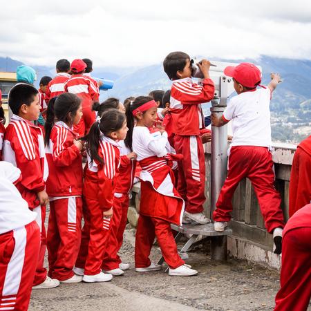 CUENCA, ECUADOR - JAN 9, 2015: Unidentified Ecuadorian children in sport clothes look through the telescope. 71,9% of Ecuadorian people belong to the Mestizo ethnic group