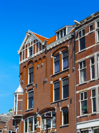 Old historical bend building in the capital of the Netherlands, Amsterdam Фото со стока