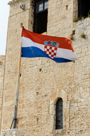 Croatian flag on the Cathedral of St. Lawrence (Katedrala Sv. Lovre), a Roman Catholic triple-naved basilica constructed in Romanesque-Gothic in Trogir, Croatia. UNESCO World heritage Stock Photo