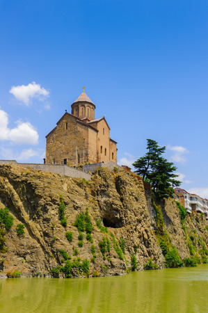 Metekhi Church on the elevated cliff that overlooks the Mtkvari river, one of the most popular landmarks of Tbilisi Фото со стока