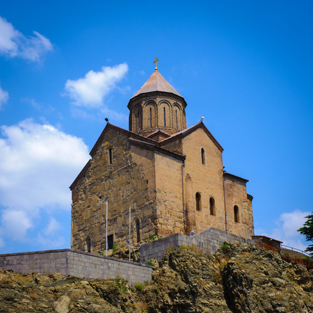 Metekhi Church on the elevated cliff that overlooks the Mtkvari river, one of the most popular landmarks of Tbilisi Stock Photo