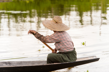 Burmese woman in bamboo boat sails over the Inle Sap,a freshwater lake in the Nyaungshwe Township of Taunggyi District of Shan State, Myanmar