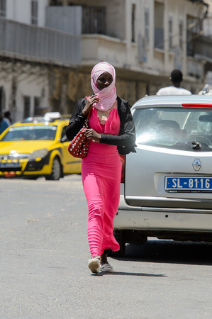 SAINT LOUIS, SENEGAL - APR 24, 2017: Unidentified Senegalese woman in pink dress and headscarf walks along the street in the centre of Saint Louis, one of the major cities in Senegal
