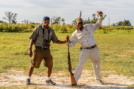 OKAVANGO DELTA, BOTSWANA - JAN 11, 2016: Unidentified Botswana men with gun and smile. They work to protect people from the wild animal at the Moremi Game Reserve
