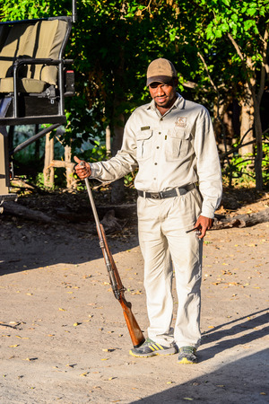 OKAVANGO DELTA, BOTSWANA - JAN 11, 2016: Unidentified Botswana man holds the gun. He works to protect people from the wild animal at the Moremi Game Reserve Editorial