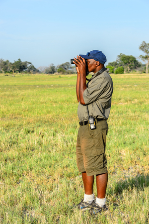 OKAVANGO DELTA, BOTSWANA - JAN 11, 2016: Unidentified Botswana man take picture of the Moremi Game Reserve. The popular safari destination