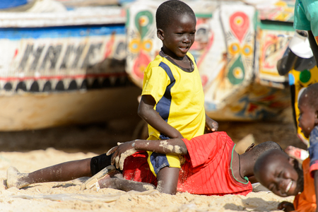 KAYAR, SENEGAL - APR 27, 2017: Unidentified Senegalese little boys lie on the sand while playing on the coast of the Atlantic Ocean. Many Kayar people work in port
