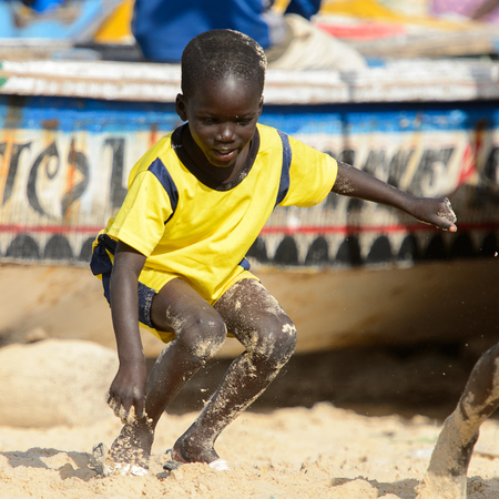 KAYAR, SENEGAL - APR 27, 2017: Unidentified Senegalese little boy in yellow shirt plays in sand on the coast of the Atlantic Ocean. Many Kayar people work in port