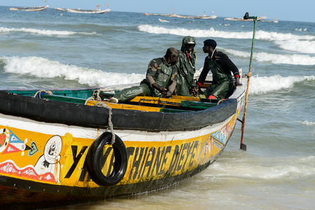 KAYAR, SENEGAL - APR 27, 2017: Unidentified Senegalese men sail on the boat on the coast of the Atlantic Ocean. Many Kayar people work in port Editorial