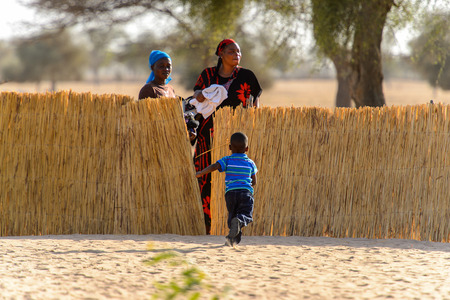 FERLO DESERT, SENEGAL - APR 25, 2017: Unidentified Fulani little boy in blue shirt runs to his mother . Fulanis (Peul) are the largest tribe in West African savannahs