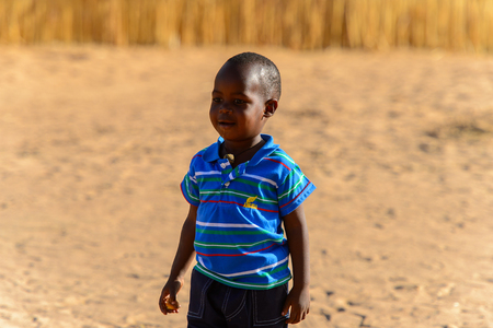 FERLO DESERT, SENEGAL - APR 25, 2017: Unidentified Fulani little boy in blue shirt walks along the village . Fulanis (Peul) are the largest tribe in West African savannahs