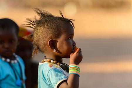 FERLO DESERT, SENEGAL - APR 25, 2017: Unidentified Fulani little girl eats fruit. Fulanis (Peul) are the largest tribe in West African savannahs