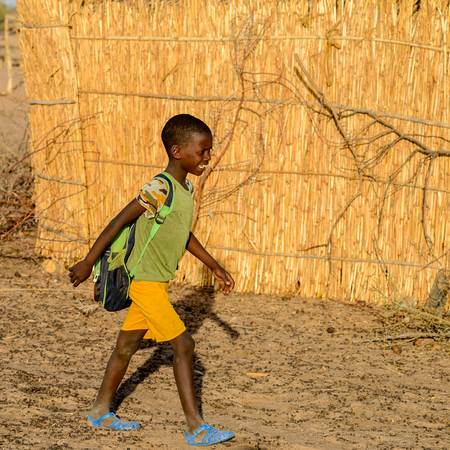 FERLO DESERT, SENEGAL - APR 25, 2017: Unidentified Fulani little boy with backpack walks along the street. Fulanis (Peul) are the largest tribe in West African savannahs